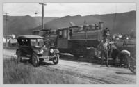 Two train locomotives and automobile
