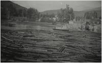 "Log boom in Sicamous Channel at foot of Finlayson St. Tordoff house to right on Channel ""MPF"" tugboat with boom"