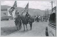 Two unidentified indigenous persons on horses hold the Union Jack and American flag